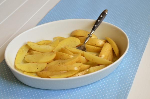 Kartoffelspalten mit Öl, Salz und Pfeffer in der Form