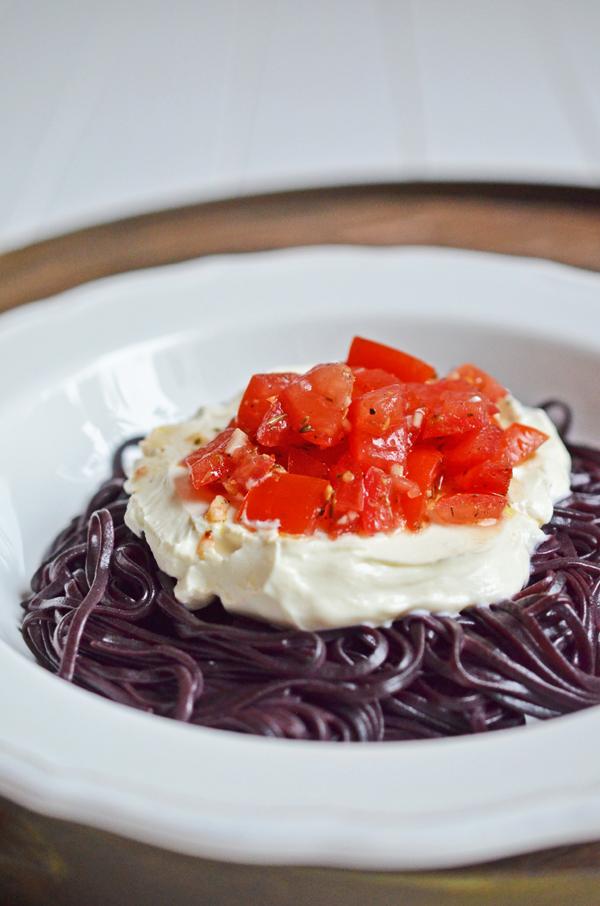 Abendtüte: schwarze Reisnudeln mit Tomaten und Ziegenfrischkäse